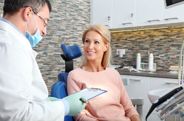 Woman talking to dentist during dental exam at Dr. Kurt Gibson, DDS, Winston-Salem, NC